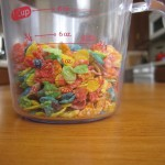Photograph of Fruity Pebbles breakfast cereal in a 1-cup measuring cup.