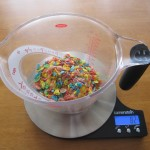 Photograph of Fruity Pebbles in a large measuring cup on a scale.