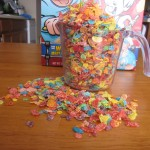 Photograph of Fruity Pebbles overflowing a small measuring cup.